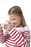 Schönes weibliches Kind mit dem blonden Haar und den blauen Augen unter Verwendung des Handys, der Spiel spielt Lizenzfreies Stockfoto