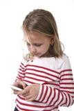 Schönes weibliches Kind mit dem blonden Haar und den blauen Augen unter Verwendung des Handys, der Spiel spielt Lizenzfreies Stockbild