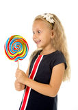 Schönes weibliches Kind mit dem langen blonden Haar, welches das enorme gewundene Lutschersüßigkeitslächeln glücklich hält Stockbild