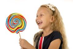 Schönes weibliches Kind mit dem langen blonden Haar, welches das enorme gewundene Lutschersüßigkeitslächeln glücklich hält Lizenzfreies Stockbild