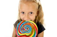 Schönes weibliches Kind mit dem langen blonden Haar, welches das enorme gewundene Lutschersüßigkeitslächeln glücklich hält Stockbilder