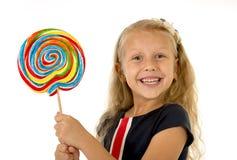 Schönes weibliches Kind mit dem langen blonden Haar, welches das enorme gewundene Lutschersüßigkeitslächeln glücklich hält Lizenzfreie Stockbilder