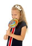 Schönes weibliches Kind mit dem langen blonden Haar, welches das enorme gewundene Lutschersüßigkeitslächeln glücklich hält Stockfotos