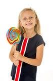 Schönes weibliches Kind mit dem langen blonden Haar, welches das enorme gewundene Lutschersüßigkeitslächeln glücklich hält Stockfoto