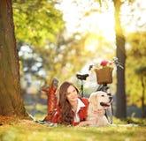 Schönes weibliches Lügen auf Gras mit ihrem Hund in einem Park Lizenzfreie Stockfotos