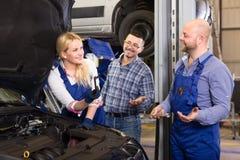 Schönes weibliches Mechanikerfestlegungsauto Stockfoto