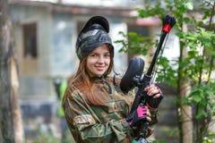 Schönes weibliches Modell, das draußen in der Paintballmunition aufwirft lizenzfreies stockfoto