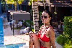 Schönes weibliches Modell, das durch das Pool aufwirft getont in den warmen Farben, schoss draußen horizontal Lizenzfreie Stockfotografie
