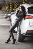 Schönes weibliches Modell, das an einem weißen Auto in der sexy Haltung steht Stockbild