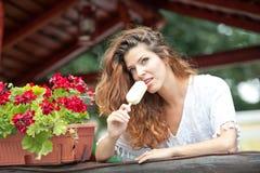 Schönes weibliches Porträt mit dem langen braunen Haar, das Eiscreme nahe einem Topf mit den roten Blumen im Freien isst Attrakti Stockbilder