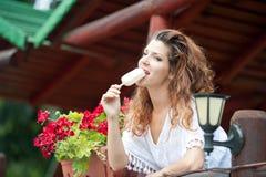 Schönes weibliches Porträt mit dem langen braunen Haar, das Eiscreme nahe einem Topf mit den roten Blumen im Freien isst Attrakti Stockfotografie
