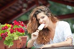 Schönes weibliches Porträt mit dem langen braunen Haar, das Eiscreme nahe einem Topf mit den roten Blumen im Freien isst Attrakti Lizenzfreie Stockfotografie