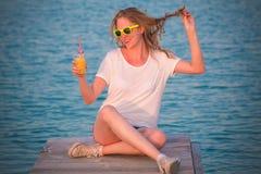 Schönes weibliches Sitzen auf Dock- und Holdingglas orange jui Stockbild