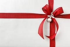 Schönes Weihnachtsgeschenkgeschenk mit hellem rotem Bogen und silberner Packpapierhintergrundgrenze stockfotos