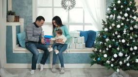 Schönes Weihnachtsglückliche Familie mit kleinem Mädchen in den gestrickten Strickjacken, die auf dem Fensterbrett sitzen stock footage