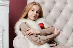 Schönes Weihnachtsmädchen, das ein Spielzeug sitzt in einem weißen Stuhl nahe dem Kamin und dem Weihnachtsbaum umarmt Lizenzfreie Stockfotos