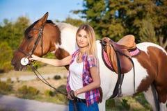 Schönes Weinleset-shirt und -jeans junger Dame tragendes, die a reiten Stockbild