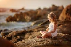 Schönes wenig Engel gir, das auf einem Felsen sitzt und den Abstand untersucht stockfoto
