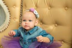 Schönes wenig intelligentes Mädchensitzen Stockfoto