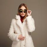 Schönes Wintermädchen im weißen Pelz und in der Sonnenbrille Schönes Mädchen lokalisiert auf weißem Hintergrund Junge Frau 15 Stockbild