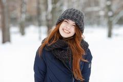 Schönes Winterporträt der Nahaufnahme der jungen entzückenden lächelnden Rothaarigefrau im schneebedeckten Park des netten Strick stockfotos