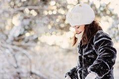 Schönes Winterporträt des Kindermädchens im sonnigen Winterwald spielt mit Schnee Lizenzfreies Stockfoto