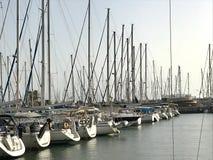 Schönes Yachtschiff festgemacht am Hafen mit anderen Booten auf blauem gesalzenem Meer lizenzfreie stockfotografie