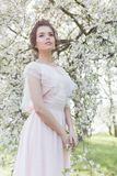 Schönes zartes süßes Mädchen in einem rosa Kleid mit einem nahen blühenden Baum der Frisur an einem sonnigen Frühlingstag Stockbild