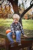 Schönes zufälliges blondes Kindersitzen im Freien auf Tabelle und Lachen Herbst Stockbilder