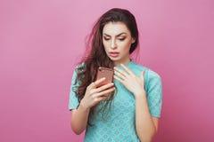 Schönheit überraschte oder entsetzte die frohe Frau mit nacktem Make-up des langen Haares im Eyewear, der zuhause mit ihrem Smart Lizenzfreie Stockbilder