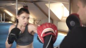 Schönheit übt, mit ihrem Trainer in der Turnhalle zu boxen Ansicht von den Trainern ziehen sich zurück stock video