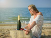 Schönheit auf dem Strand mit einer Flasche kaltem Champagner und Erdbeeren Lizenzfreies Stockfoto