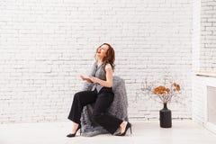Schönheit benutzt eine digitale Tablette und lächelt beim Sitzen auf dem Lehnsessel am modernen Innenraum stockfoto