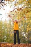 Schönheit blonde Throws verlässt im Park im Herbst Stockfotos