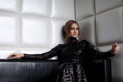 Schönheit Brunettefrau auf Sofa im Nachtklub lizenzfreie stockfotografie