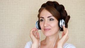 Schönheit in den Kopfhörern hörend auf ein musikalisches Lied auf hellem Hintergrund stock video