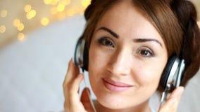 Schönheit in den Kopfhörern hörend auf ein musikalisches Lied auf hellem Hintergrund stock footage
