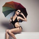 Schönheit in der Badebekleidung und Sonnenbrille, die Regenschirm hält Stockfotos