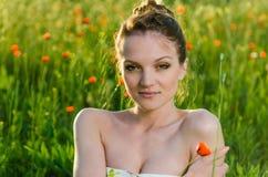 Schönheit der jungen Frau auf dem Mohnblumengebiet Lizenzfreies Stockbild