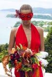 Schönheit in der Karnevalsmaske mit Blumenstrauß Lizenzfreies Stockbild