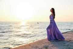 Schönheit in der purpurroten flüssigen Kleiderstellung auf dem Strand stockfotos