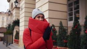 Schönheit in der roten Winterjacke geht entlang die Straße, die mit Schnee in einer schönen alten europäischen Stadt bedeckt wird stock video