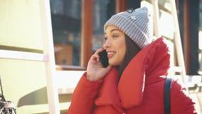 Schönheit in der roten Winterjacke steht auf der Straße, die mit Schnee bedeckt wird und spricht auf dem Smartphone an einem hell stock video