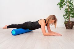Schönheit in der Sportkleidung, Pilates-Lehrer, der mit Schaumrolle ausdehnt und aufwärmt Die Plankenübung mit Betonung auf stockfotos