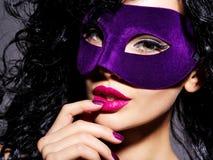Schönheit in der violetten Theatermaske auf Gesichts- und Purpurnägeln Lizenzfreie Stockfotos