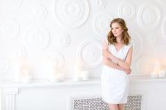 Schönheit in der weißen Aufstellung für ein Bild, das Sehvermögen weg verwiesen, weiße Wand und Kerzen hinter ihr lizenzfreie stockfotos
