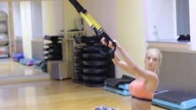 Schönheit, die Übungen mit einer harten Suspendierung mit Eignungsbügeln in der Turnhalle tut stock video footage