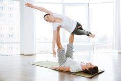 Schönheit, die acro Yoga mit Partner tuend balanciert Lizenzfreies Stockbild