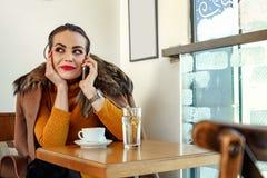 Schönheit, die allein im Café sitzt und über Smartphone spricht Stockfoto