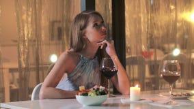 Schönheit, die auf Abendtische im Restaurant und in trinkendem Rotwein sitzt stock footage